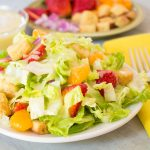 Salad with strawberries and mandarin oranges with mango coconut dressing on white plate