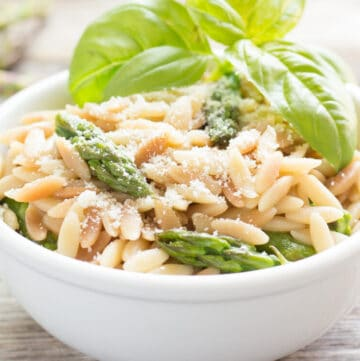 Toasted Orzo and asparagus tips on a white bowl with a basil garnish