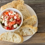 Tomato Mozzarella Bruschetta in white bowl and bread on white plate