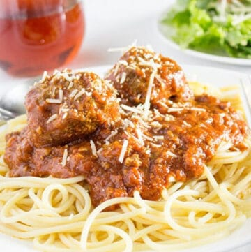 Spaghetti and meatballs on white plate with salad and a glass of wine