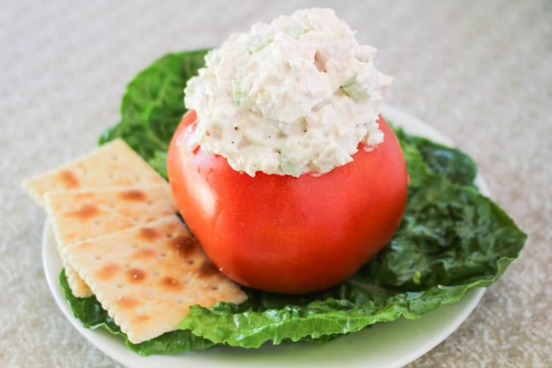 Chicken Salad in a tomato cup with cracker on lettuce bed