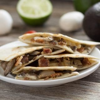 acon and mushroom quesadilla pices on white plate