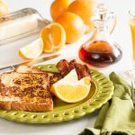 Plated Orange French Toast on green plate set on breakfast table