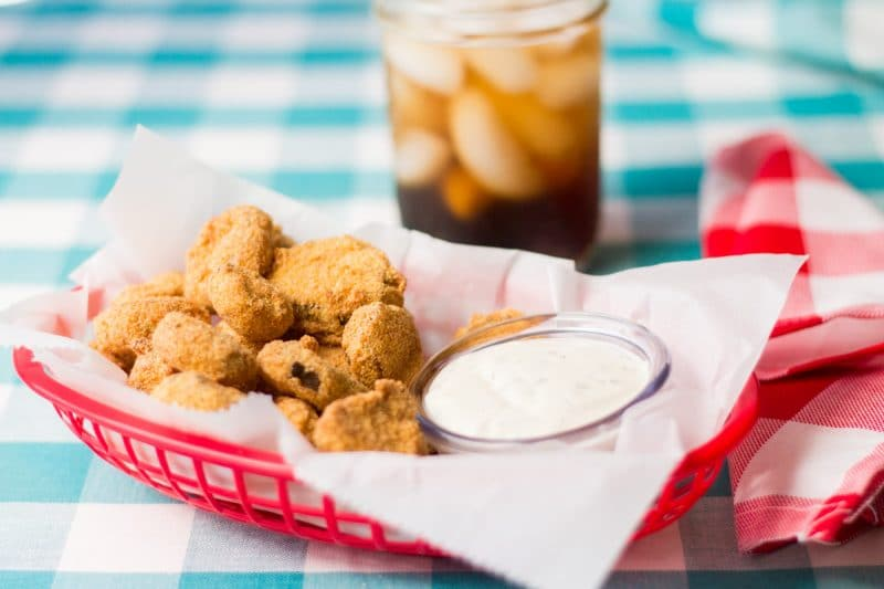 Sweet and Spicy Fried Pickles with sauce in red basket and sweet tea