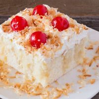 Close-up Cream of Coconut Cake with cherries and toasted coconut on white plate