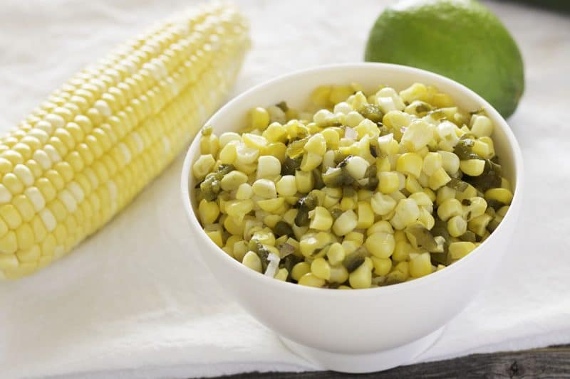 Corn and roasted poblano salsa in white bowl, corn cob and lime behind