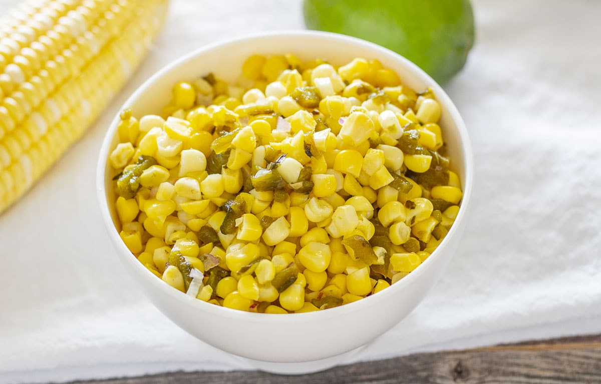 Corn salsa in a white bowl with fresh corn and lime in the background
