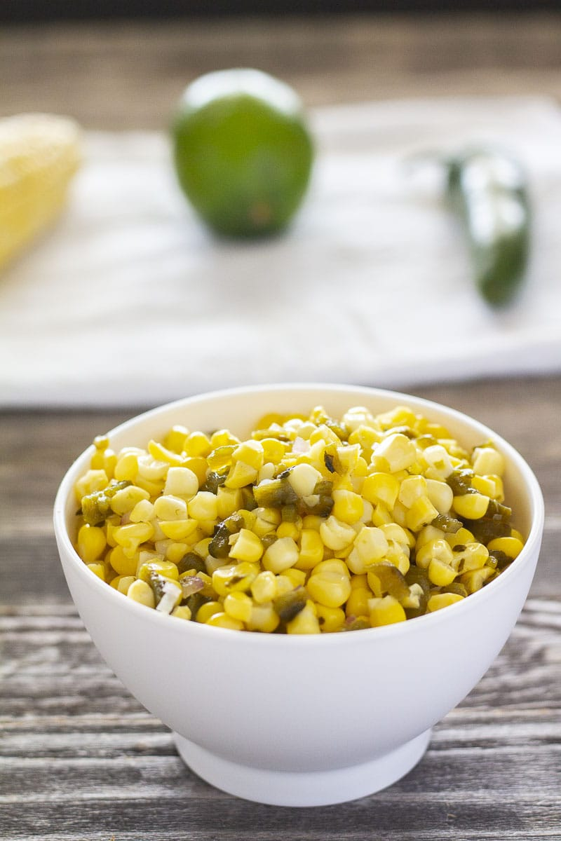 Yellow corn with roasted pepper pieces in a white bowl