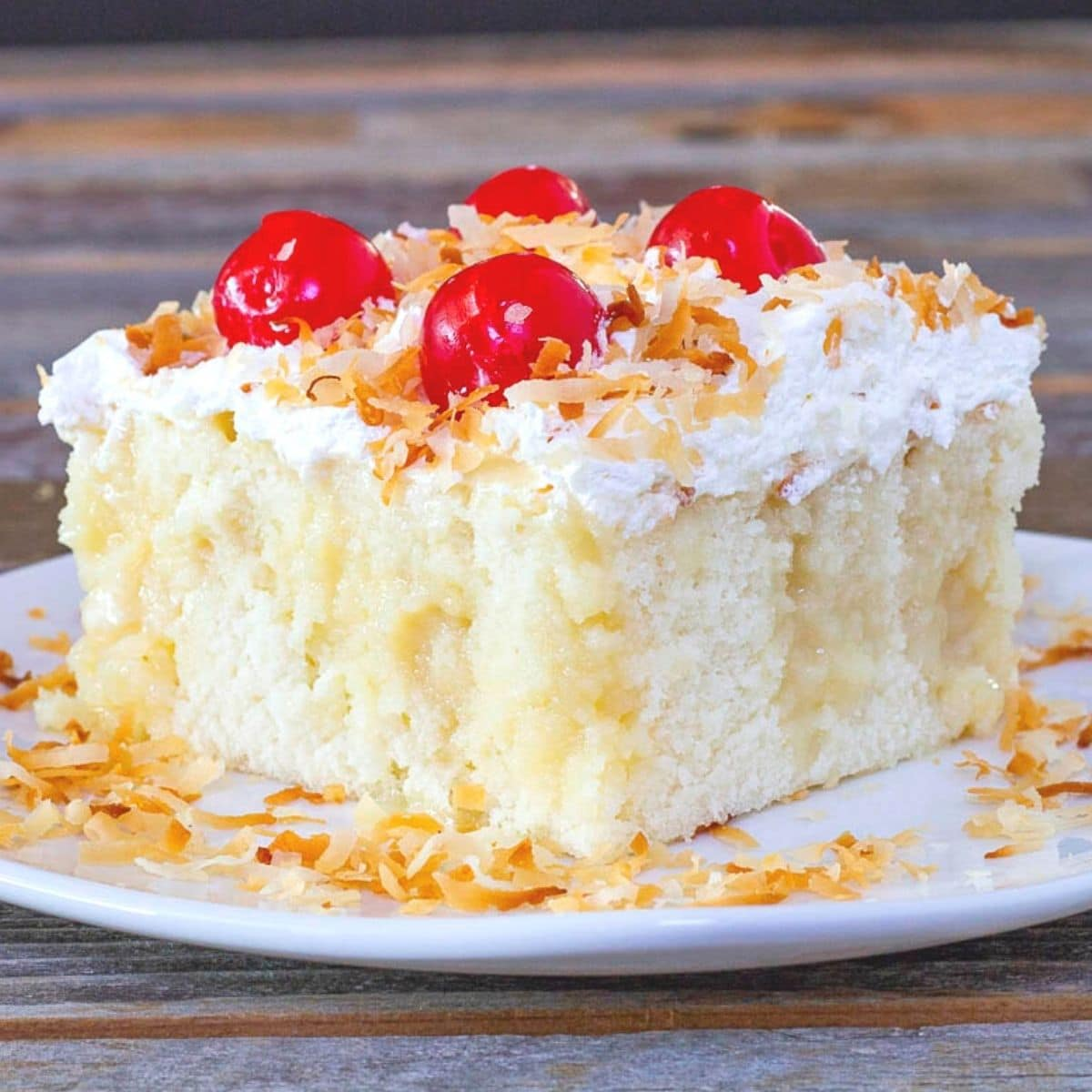 Piece of coconut cake topped with cherries