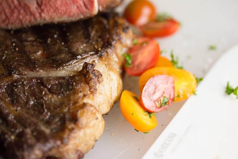 Rib eye on a plate with tomatoes