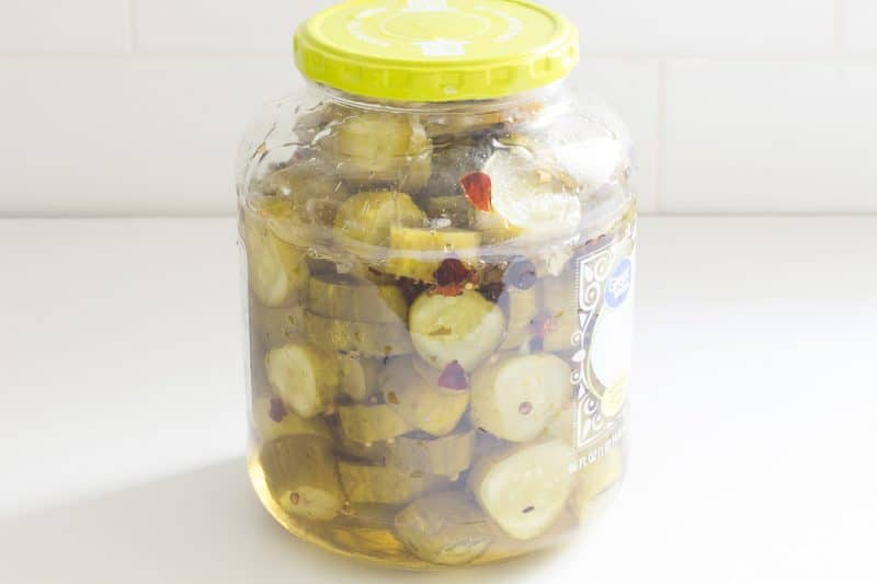 Sliced pickles i a jar covered with spicy syrup