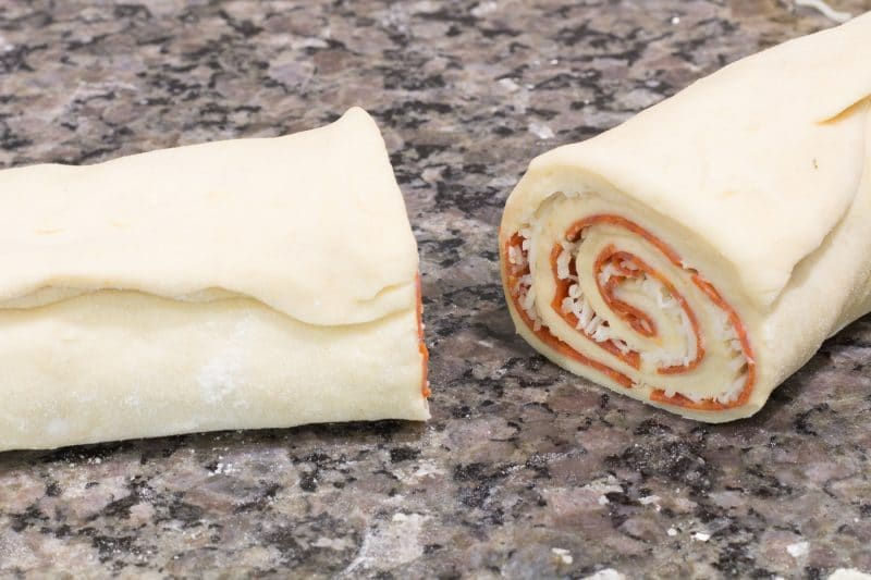 pepperoni pizza rolls sliced in half on a granite countertop