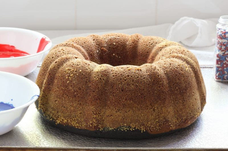 Butter Pound Cake on a baking sheet with bowls of colored glaze and sprinkles