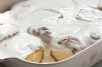 Cinnamon rolls with vanilla icing in a baking pan