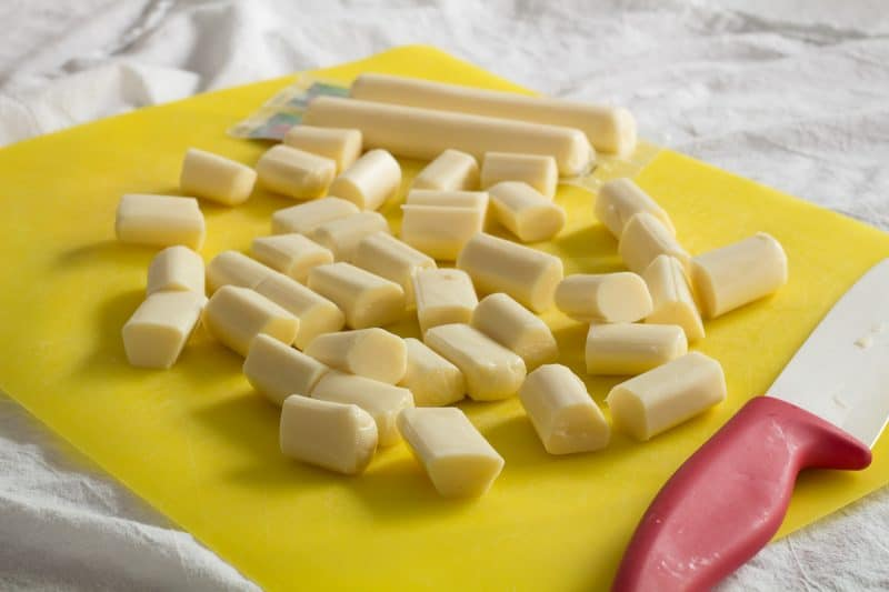 cheese sticks cut into pieces on a yellow cutting mat