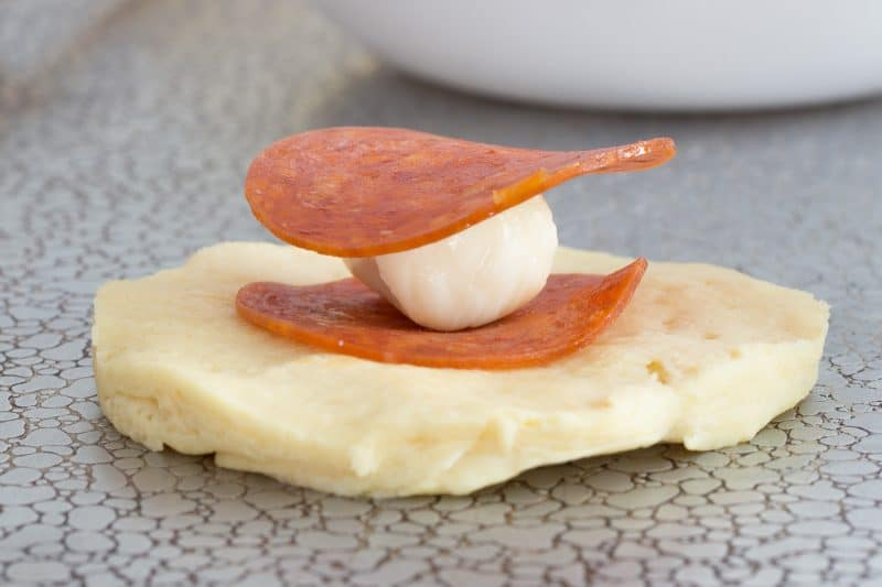 mozzarella cheese chunk between pepperoni slices on a refrigerated biscuit