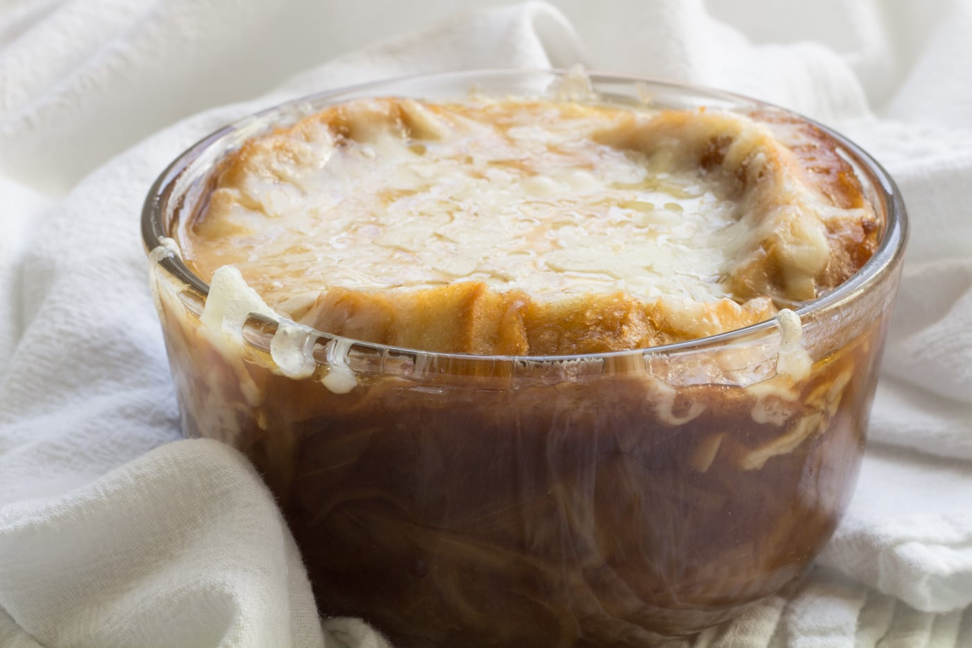 French Onion Soup in a glass bowl on a white tea towel