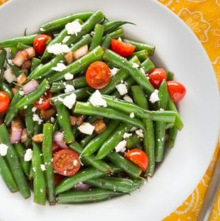 Overhead shot of green bean salad in a white bowl with a spoon on a yellow patterned cloth
