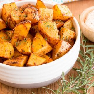 Paprika oven roasted potatoes in a white bowl with sour cream dipping sauce and rosemary sprigs