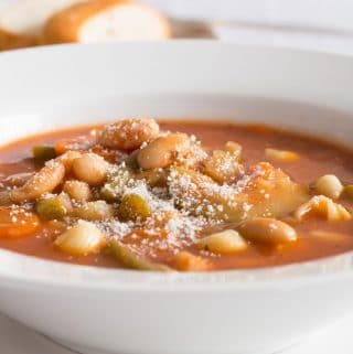 Side view of minestrone soup in a wide rimmed white bowl