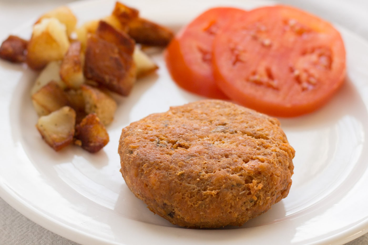 Salmon Patties with home fries and tomato slices on a white plate