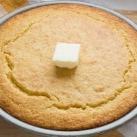 Buttermilk Cornbread topped with a pat of butter in a pie tin