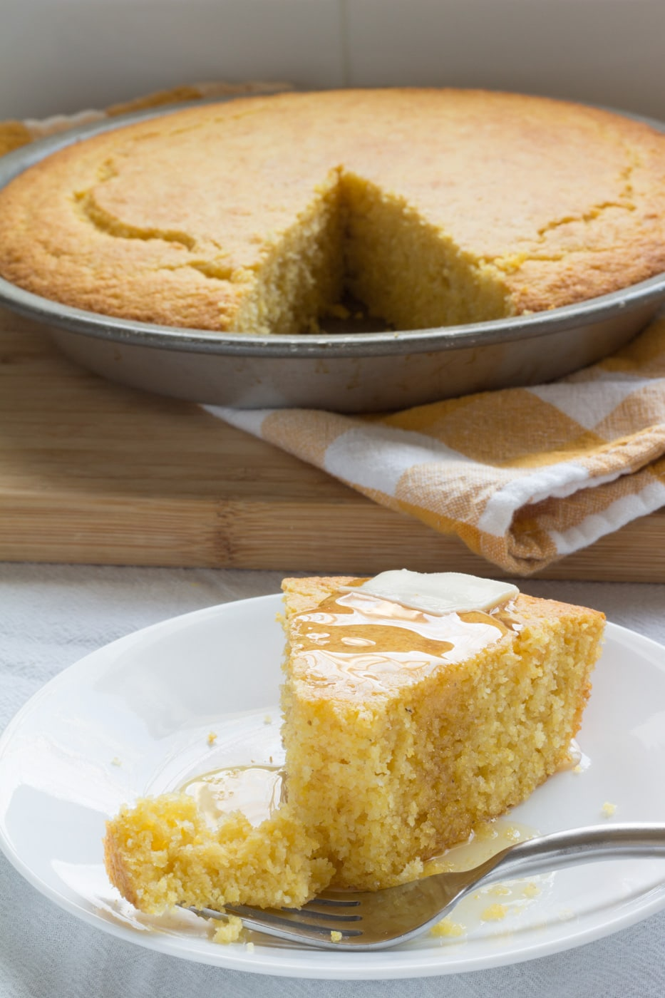 Sweet Southern Cornbread with butter and honey on a white plate with a fork and cornbread in a pie pan in the background