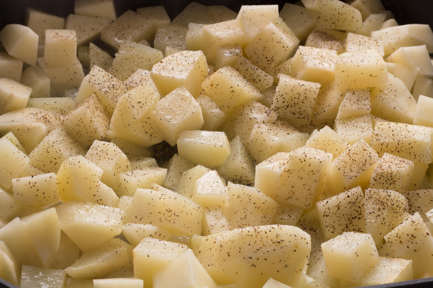Diced potatoes with black pepper and oil