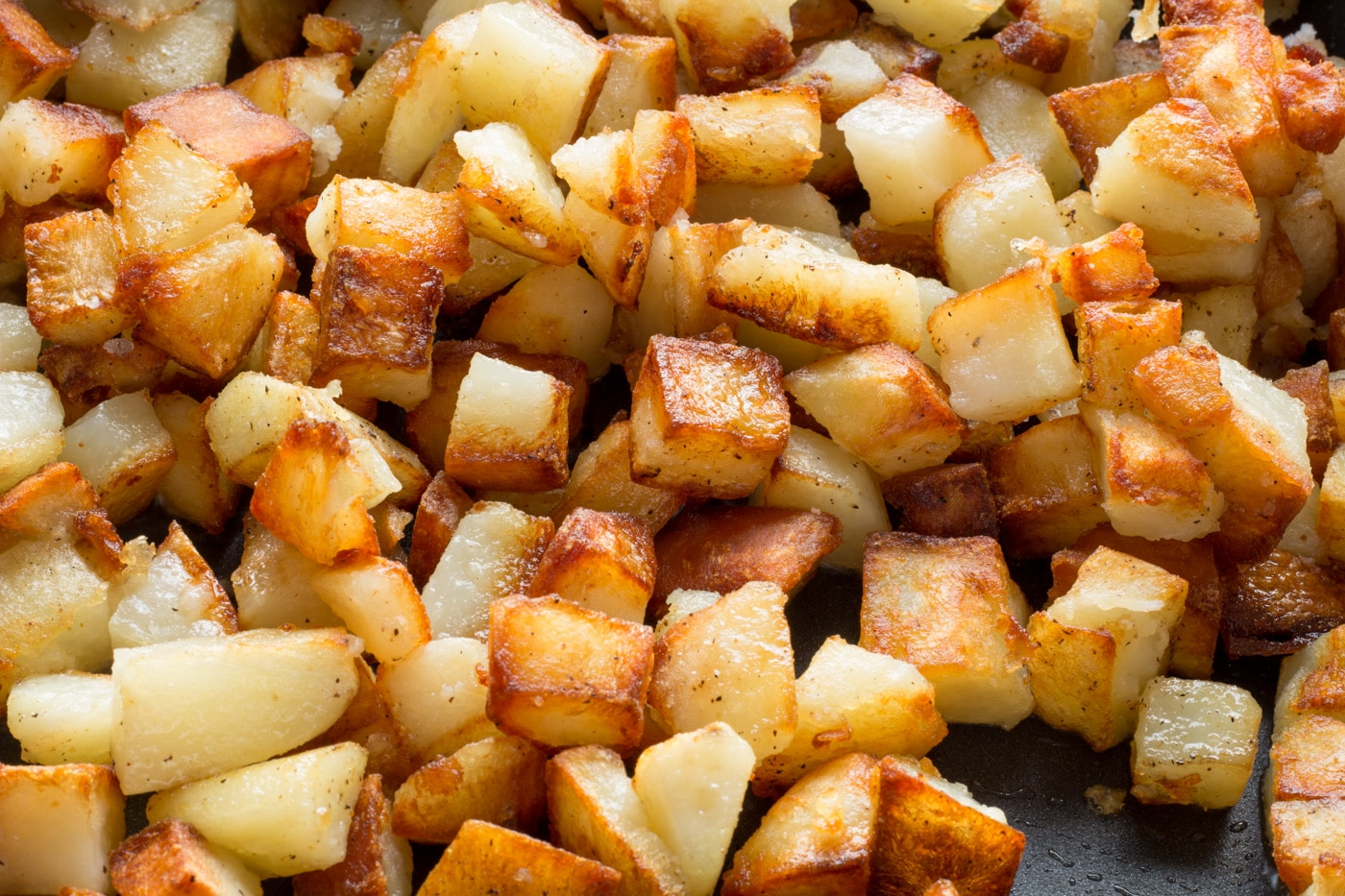 Fried diced potatoes in an electric skillet