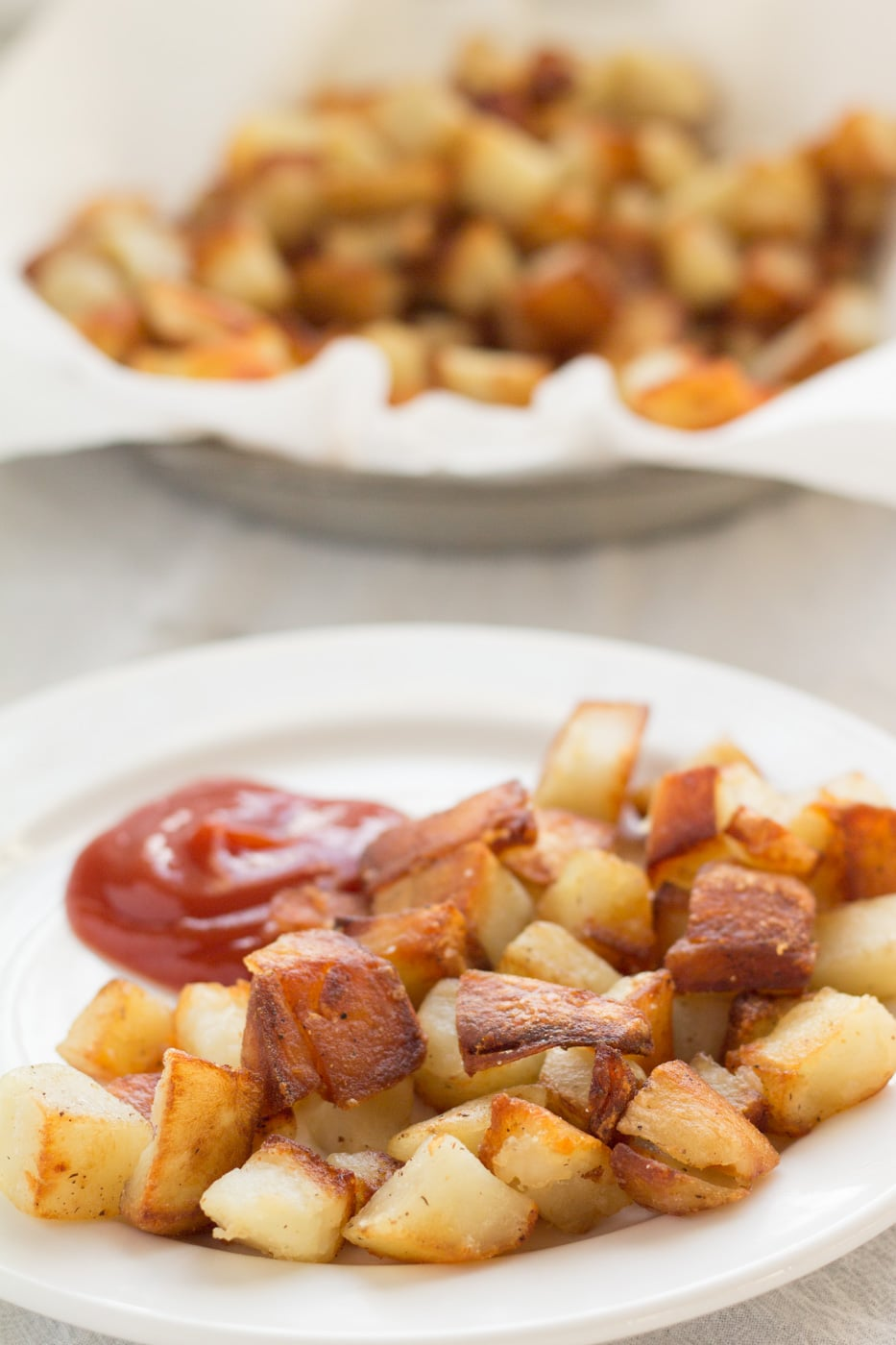 Home fries with ketchup on a white plate with blurred fried potatoes in a pie tin in the background