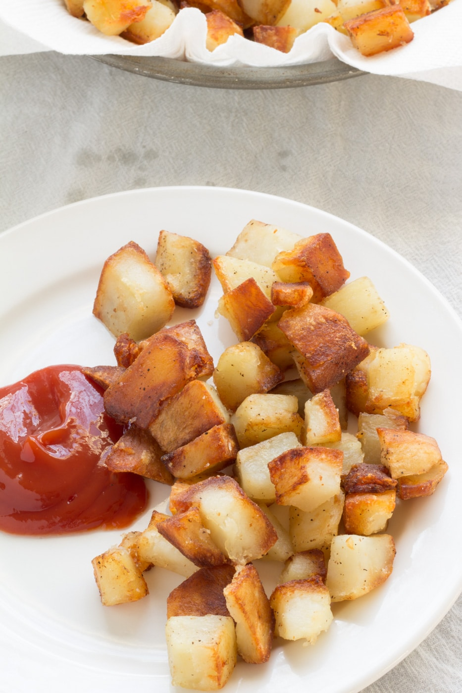 Home fries with ketchup on a white plate