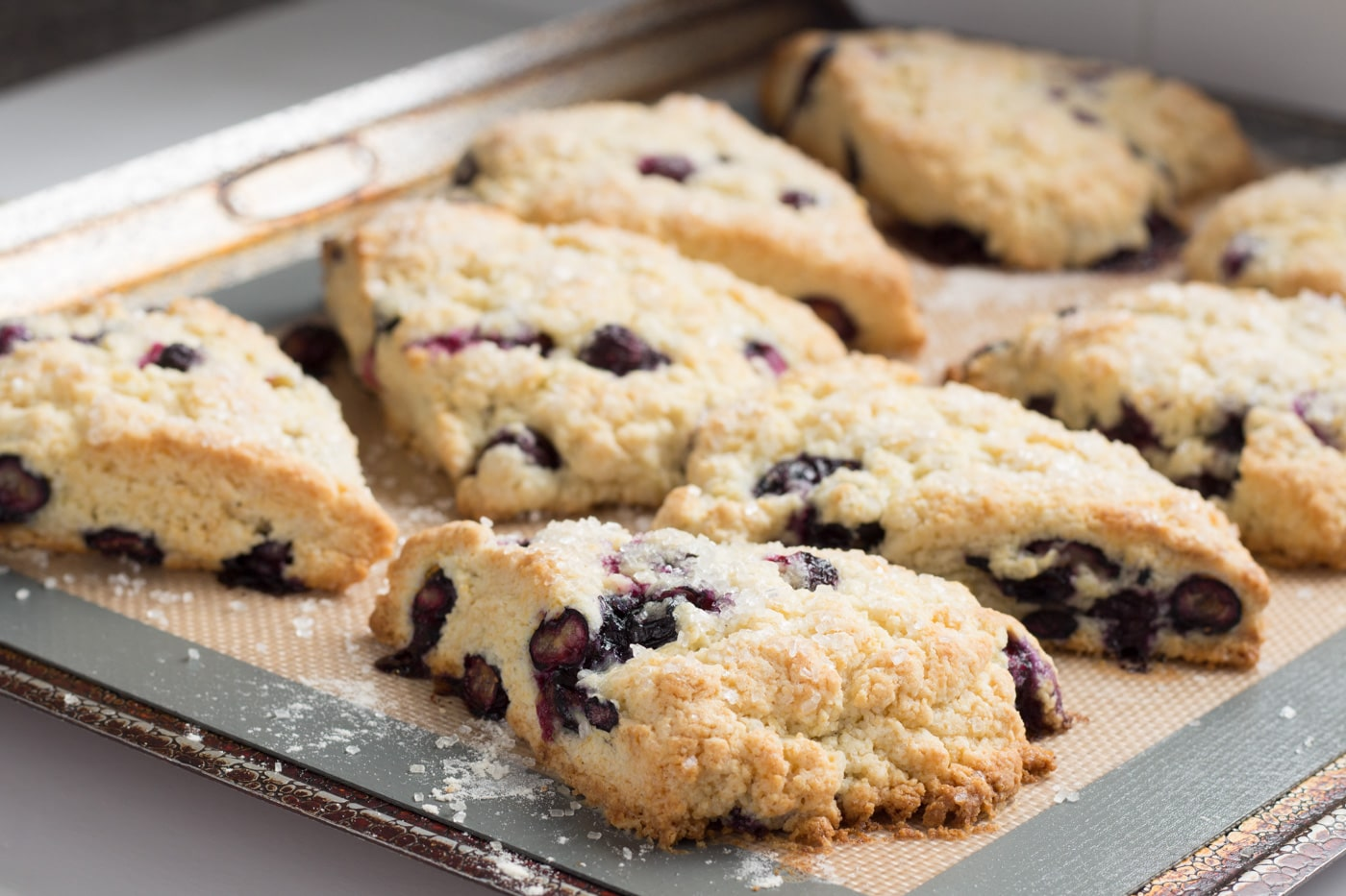 Side view of baked blueberry scones on a baking sheet