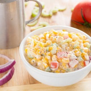 Creamy corn salad on a wooden board with red onion pieces, sliced celery, tomato half, and a pepper shaker on a wooden board