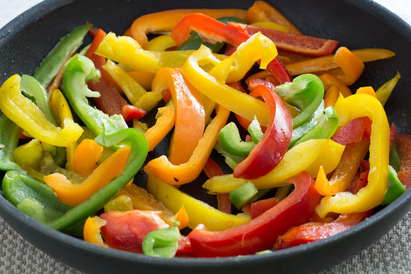 Sliced green, red, orange, and yellow peppers in a black pan