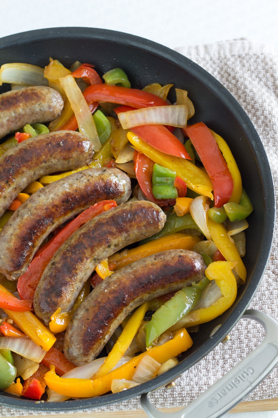 Italian Sausage links with peppers and onions in a black skillet