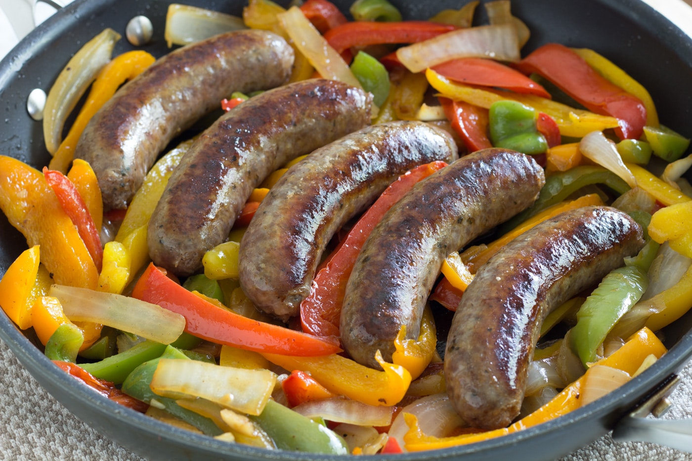 Seared Italian sausage ontop of bells peppers and onions in a pan.