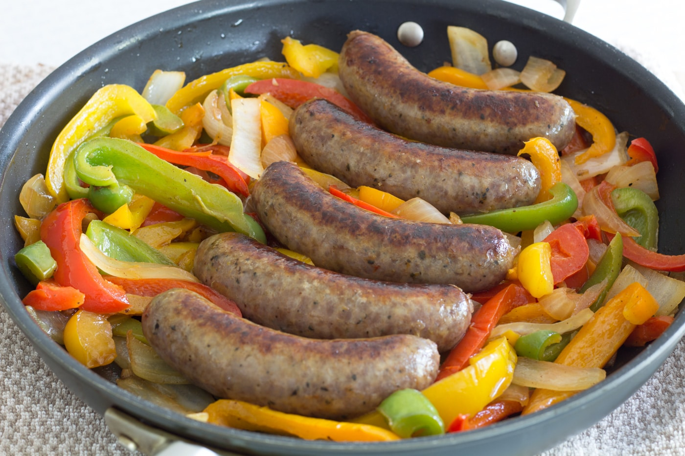 5 Italian Sausage links on top of mixed bell peppers and onions in a skillet