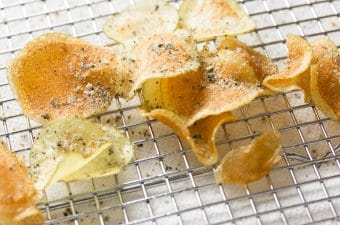 Homemade kettle chips sprinkled with seasonings on a cooling rack