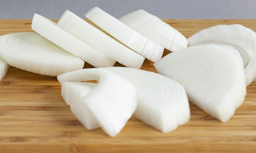 Sliced white onions on a cutting board