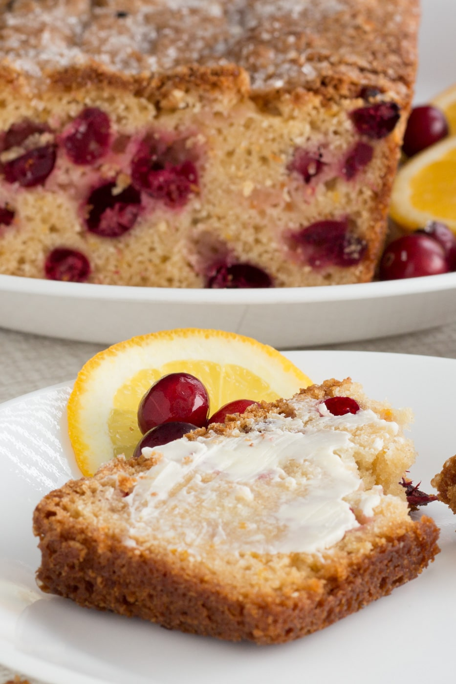Cranberry quick bread slice with butter on a plate with cranberries and orange slices