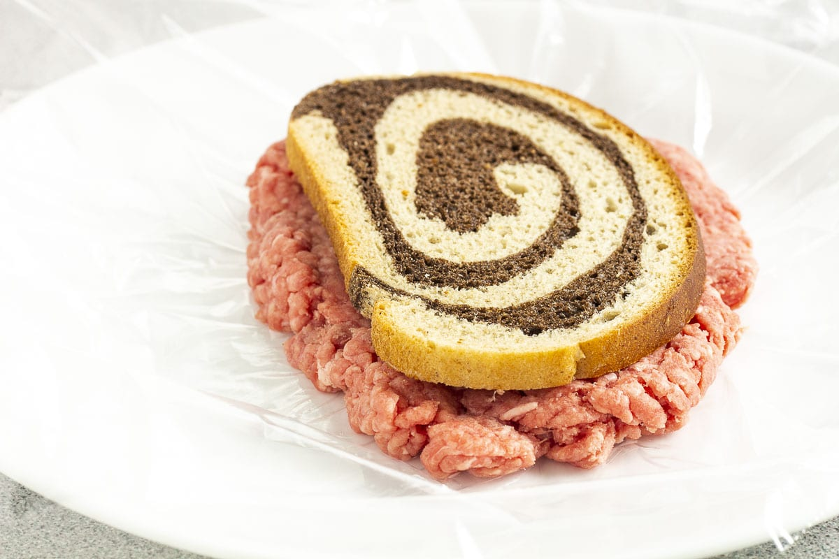 Ground beef patty and swirled rye bread on a plate