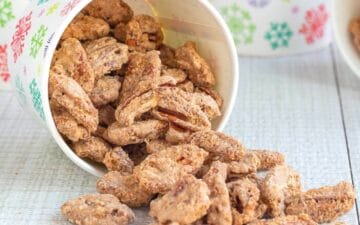 Candied pecans spilling out of a paper cup