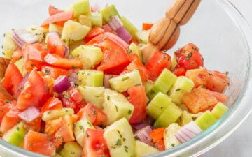 Diced cucumbers and tomatoes covered in dressing in a bowl with a wooden salad spoon