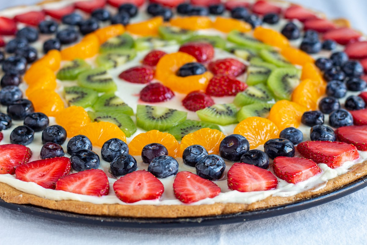 sugar cookie pizza topped with cream cheese and fruit